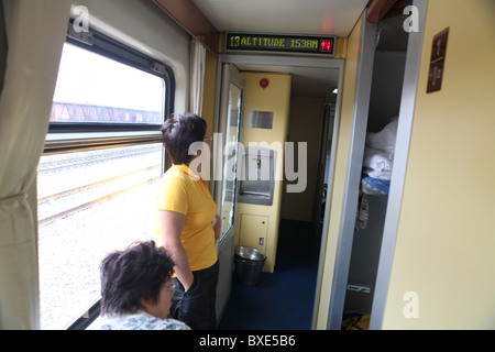 Passengers check the altitude on the Qinghai - Xizang train, the world's highest railway, here between Chengdu and - Stock Photo