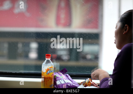 Passenger on the Qinghai - Xizang train, the world's highest railway, here between Chengdu and Lhasa, Tibet. - Stock Photo