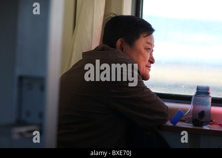 Chinese passenger on the Qinghai - Xizang train, the world's highest railway, here between Chengdu and Lhasa, Tibet. - Stock Photo
