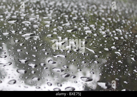 Rain droplets on a cars paintwork. - Stock Photo