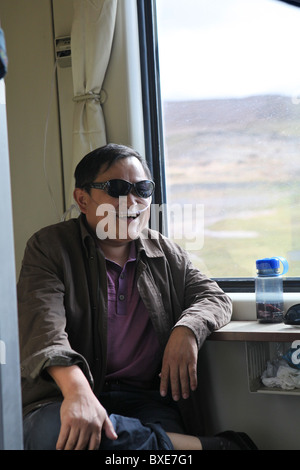 Passenger breathing oxygen on the Qinghai - Xizang train, the world's highest railway, here between Chengdu and - Stock Photo