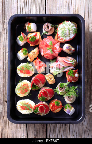 Assortment of hors d'oeuvre on a black tray - Stock Photo