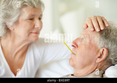 Senior woman caring for man with a fever - Stock Photo