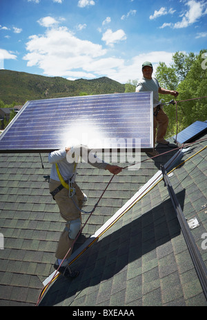 Construction workers installing solar panels on roof - Stock Photo