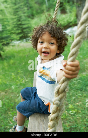 Cute young child sitting on swing - Stock Photo