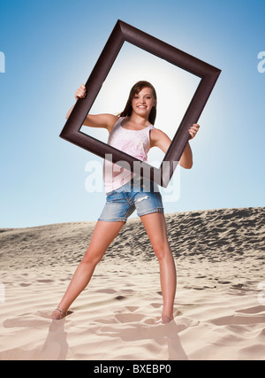 Woman standing on beach holding picture frame - Stock Photo