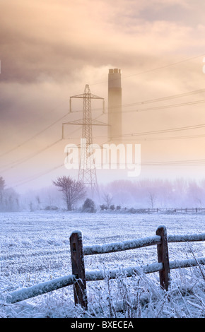 Power station chimney and electricity pylon showing through cold morning mist behind a frosty field - Stock Photo