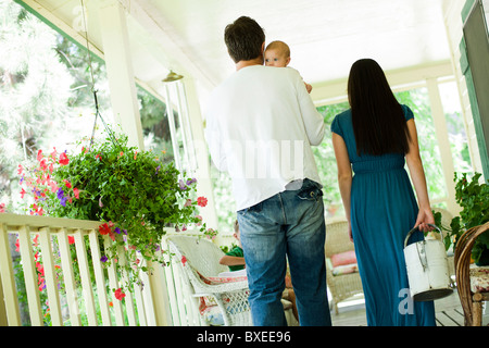Young family walking on porch - Stock Photo