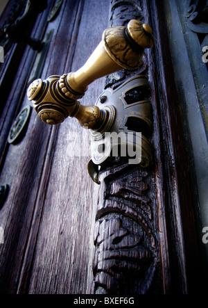 ornamental brass door handle on weathered old oak door Vienna Austria - Stock Photo