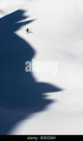 A telemark skier making turns in powder in Disentis, Switzerland. The mountains cast a shadow that looks like a - Stock Photo