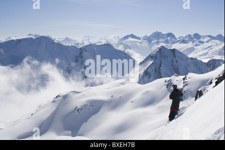 Free skier admiring the wintery mountain landscape at Andermatt, Switzerland. - Stock Photo