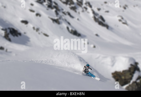A lone snowboarder making a turn on a wide, empty snowfield in Zillertall, Austria - Stock Photo