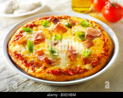 Pizza topped with 3 cheeses, Parma ham & basil. - Stock Photo
