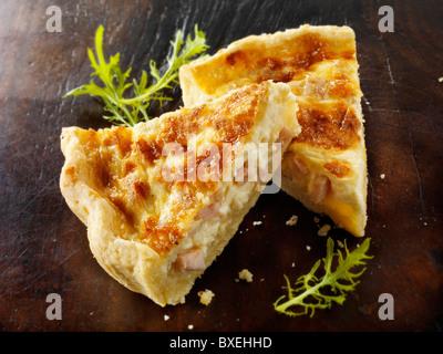 Slices of quiche Loraine on a dark wood background - Stock Photo