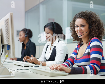 multiethnic group of female customer service representatives talking on the phone, with woman looking at camera. - Stock Photo