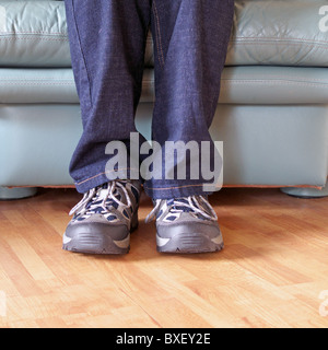 Man wearing a pair of Trainers ( Sneakers ) whilst sitting down in a leather armchair, UK MODEL RELEASED - Stock Photo