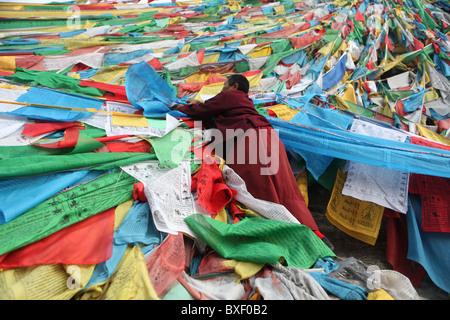 Monk with prayer flags on outer pilgrim path or Lingkhor around Iron Mountain in Lhasa, Tibet (Tibet Autonomous - Stock Photo