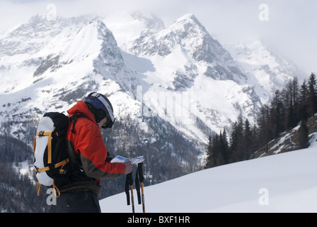 Free skier reading a map and admiring the wintery mountain landscape at Monte Rosa, Italy. - Stock Photo