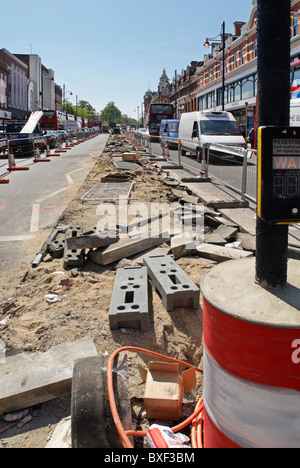 Repairing the central reservation area of Brixton Road South London UK - Stock Photo