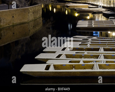 Snow-covered punts float on the River Cam in Cambridge at night - Stock Photo