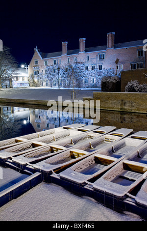 Snow-covered punts float on the River Cam in Cambridge at night, with Magdalene College behind - Stock Photo