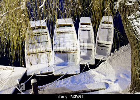 Snow-covered punts float on the River Cam under a sheltering willow tree in Cambridge at night - Stock Photo