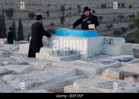 two orthodox jews praying on the tomb of or hakhaim rabbi in Mount of Olives cemetery. Jerusalem - Stock Photo