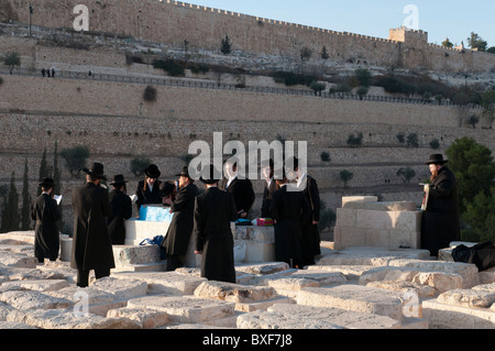 group of orthodox jews praying around a tomb at mount of olives - Stock Photo