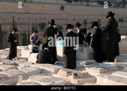 group of orthodox jews praying around a tomb at mount of olives cemetery. Jerusalem - Stock Photo