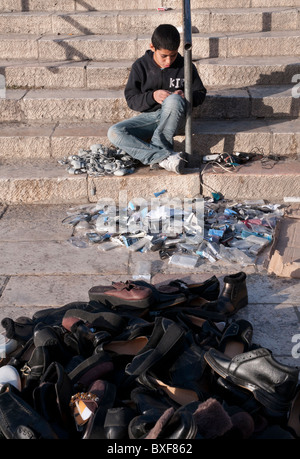 Young palestinian boy selling mobile phones accessories and shoes on the steps of Damascus Gate. Jerusalem Old City - Stock Photo