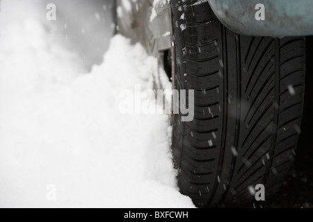 snow drifting up against a car tyre on a cold snowy winters day - Stock Photo