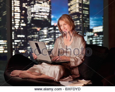 Woman in nightgown using laptop at night - Stock Photo
