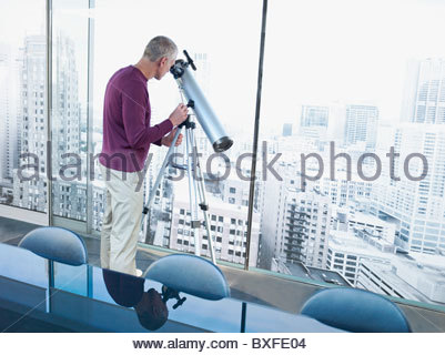 Man using telescope to look at city buildings - Stock Photo
