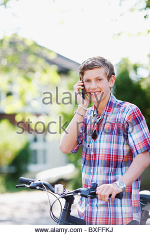 Smiling teenage boy with bicycle talking on cell phone - Stock Photo