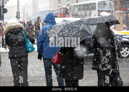 women standing at a pedestrian crossing on a cold snowy winters day Belfast city centre Northern Ireland - Stock Photo