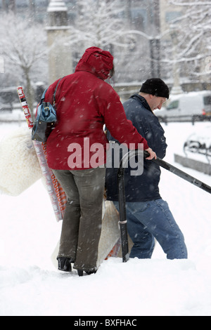 couple out christmas shopping walking down steps on a cold snowy winters day Belfast Northern Ireland - Stock Photo