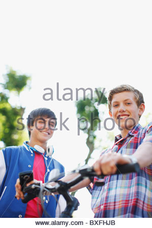 Smiling teenage boys with bicycle - Stock Photo