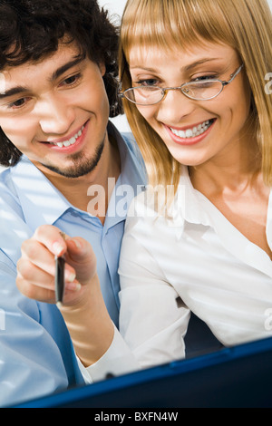 Portrait of woman with glasses and man working together - Stock Photo