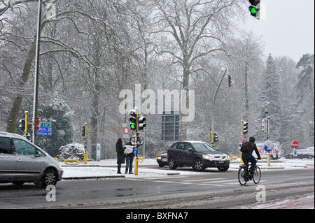 Cars and cyclist driving on slippery road in winter in the snow, Ghent Belgium - Stock Photo