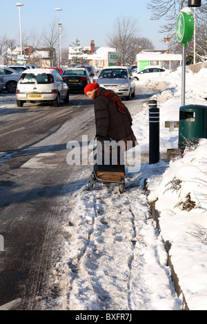 Old lady pulling shopping trolley through the snow, the wheels have left two trails behind her, dangerous conditions. - Stock Photo