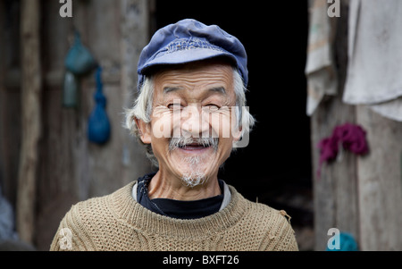 An old man outside his rustic and squalid wooden home in an isolated mountain village in Gansu province in China. - Stock Photo