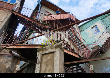Man atop Escher-like criss-crossing external metal staircases on old buildings in Tbilisi old town, Kala, Georgia. - Stock Photo