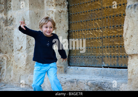 Little girl playing outside the Cathedral de Cordoba, a former medieval mosque in Cordoba, Andalusia, Spain. - Stock Photo