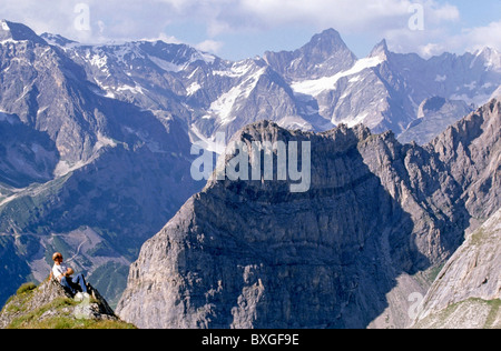 French Alps - Hiker looks down at the view from high up a mountain in the Vanoise National Park, France. - Stock Photo