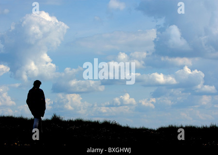 Silhouette of a lonely woman walking through countryside under a cloudy sky, France. - Stock Photo