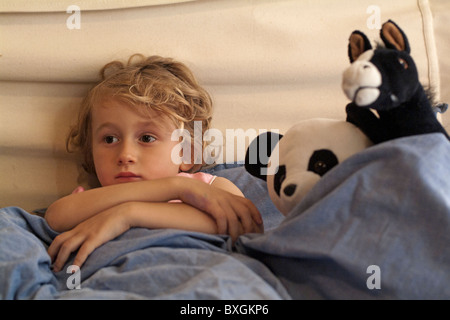 Little girl in bed watching TV surrounded by her favourite toys.