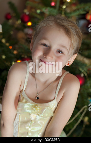 Little girl in a princess belle costume with a christmas tree in the background - Stock Photo