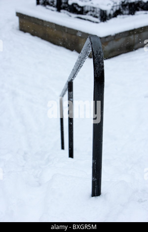 handrail on snow covered steps on a cold snowy winters day Belfast Northern Ireland - Stock Photo