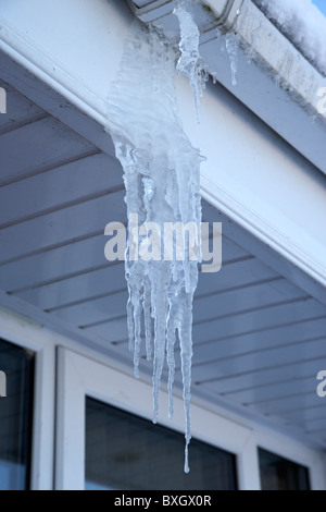 icicles hanging from pvc gutters on a cold snowy winters day Belfast Northern Ireland - Stock Photo