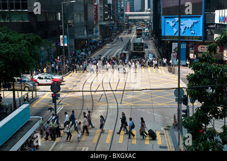 People crossing the road, Des Voeux Road, The Central, Hong Kong Island, China - Stock Photo